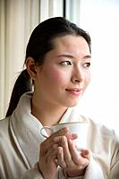 Taiwanese mid adult woman in bathrobe drinking coffee and looking out window.