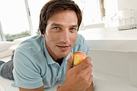 Portrait of a mid adult man wearing a hands free device and holding an apple