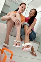 Two mid adult women sitting on steps and trying on flip_flops