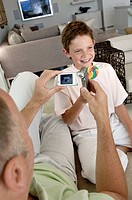 Mature man taking a picture of his son with a mobile phone