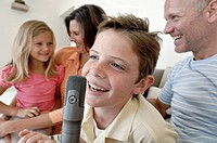 Close_up of a boy singing into a microphone with his family sitting beside him