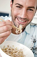 Portrait of a young man eating bean sprouts and smiling