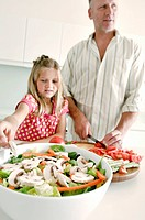 Mature man cutting vegetables in the kitchen with his daughter standing beside him