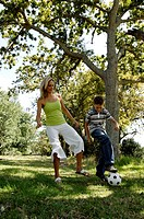 Mid adult woman playing soccer with her son in a park