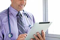 Doctor holding digital tablet in office, mid section