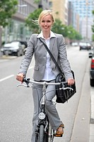 Businesswoman going to work on a bike