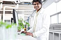 Portrait of male scientist working with plants in laboratory