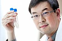 Portrait of male scientist holding test tubes in laboratory