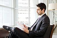 Businessman sitting in office and reading document