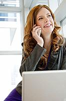 Businesswoman in office using laptop and cell phone