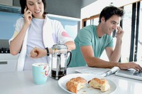 Young couple talking on mobile phones in the kitchen