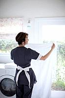 Rear view of woman in uniform doing laundry