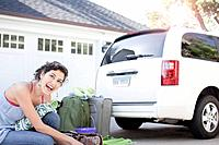 Smiling woman with luggage next to van parked in front of house