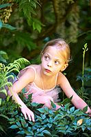 Girl in ballet costume hiding in bush