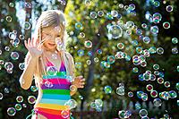 Girl 7_9 catching bubbles in park
