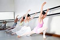 Ballet dancers posing at barre