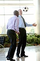 Two businessmen playing soccer in lobby