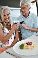 Close_up of a senior couple toasting with wine glasses and smiling at the kitchen counter