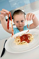 Close_up of a girl eating fettuccine at the kitchen counter