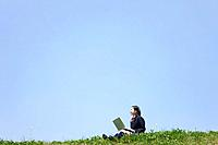 Female high school student using her laptop at the park