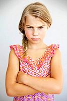 Studio portrait of serious girl 7-9 with arms crossed (thumbnail)