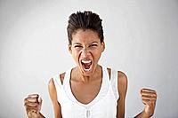 Studio portrait of woman shouting with clenched fists