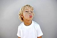 Portrait of boy 7_9 sticking out tongue, studio shot