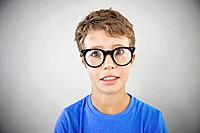 Portrait of boy 13_15 wearing glasses, studio shot