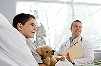 Male doctor sitting with boy 7_9 patient in hospital