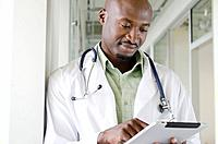 Male doctor checking medical document in hospital