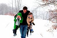 Father carrying son and daughter in snow