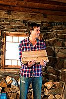 Mid adult man holding logs in rustic house