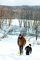 Father and son sledging on snow