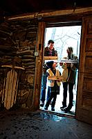 Family holding logs in doorway
