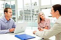 Three businesspeople meeting in office using laptop