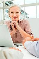 Mature businesswoman in office with laptop