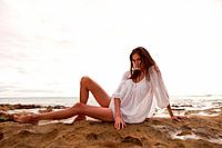 Young woman wearing white top sitting on sand, portrait