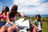 Three young friends in off road vehicle with surfboards