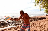 Man playing bat and ball game on beach