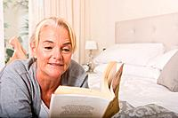 Mature woman reading in bedroom