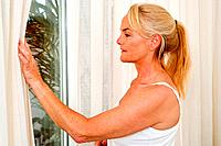 Mature woman opening curtains