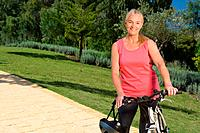 Mature woman cyclist with bicycle (thumbnail)