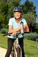 Mature woman cyclist wearing helmet and holding bottle