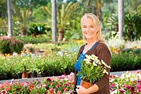 Woman with plant in pot at garden centre (thumbnail)