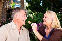 Mature woman feeding cake to husband