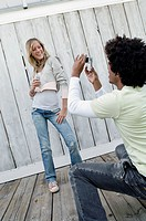 Side profile of a young man taking a picture of a young woman with a mobile phone