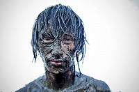 young man covered in mud at the Przystanek Woodstock - Europe´s largest open air festival in Kostrzyn, Poland