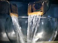 Whisky pouring from still in distillery
