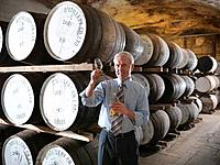Worker checking whisky in distillery