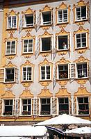 Mozart´s birthplace. House facade. Third floor. Girl seated at window. Yellow painted walls.
